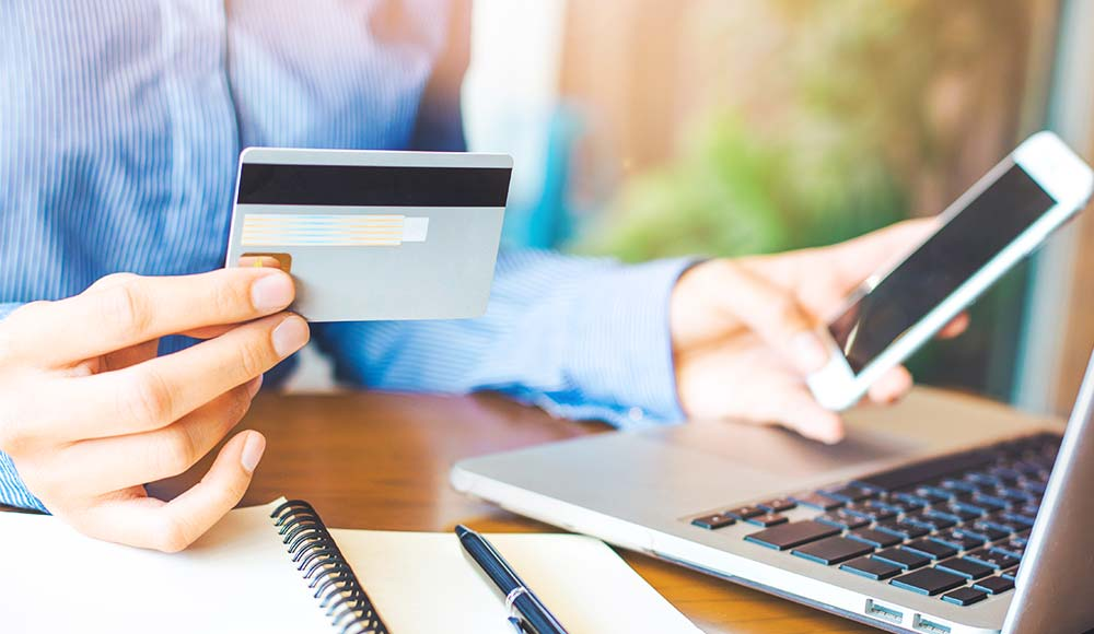 An image of a woman using her credit card on a website